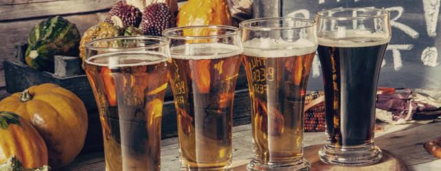 Pints of beer in front of seasonal fall vegetables.