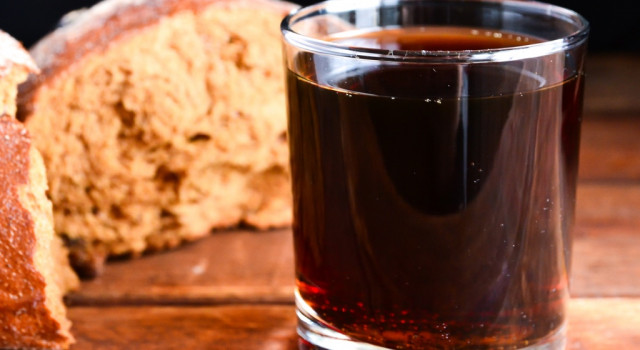 loaf of bread next to a glass of dark beer